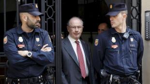 El ex jefe del Fondo Monetario Internacional, Rodrigo Rato, camina entre los oficiales de policía cuando sale de su oficina en Madrid, el 17 de abril de 2015.