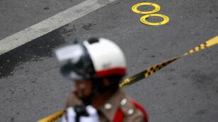Un policier surveille les restes d'un des engins explosifs, le 2 août 2019 à Bangkok.