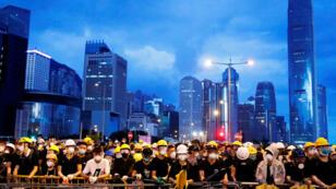 Los manifestantes contra el proyecto de ley contra la extradición se ubican detrás de una barricada durante una manifestación cerca de la ceremonia de izamiento de la bandera para el aniversario de la entrega de Hong Kong a China en Hong Kong, China, 1 de julio de 2019.