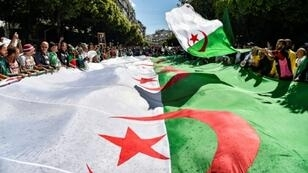 Algerian protesters march with a giant national flag during a demonstration in the capital Algiers on May 31, 2019