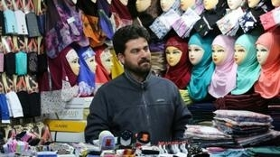 A man stands at his shop in the Shiite holy city of Qom, south of the Iranian capital Tehran, where the Islamic revolution still holds a powerful sway even as once-unthinkable signs of modernity creep into the city