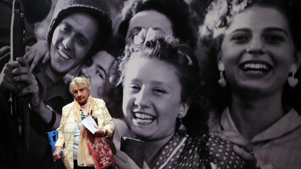 Paulette Modarresse pose devant une photo d'elle prise en 1944 à la Libération de Paris.