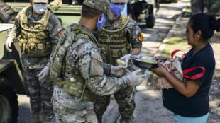 Una larga fila espera la entrega de comida que trae un camión militar. En un barrio carenciado de Quilmes, en la periferia de Buenos Aires, el aislamiento obligatorio se cumple pero el costo es alto: falta el alimento diario