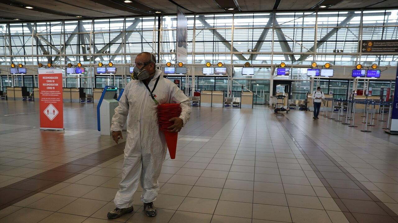 Un hombre usa un traje preventivo en el área de salidas internacionales del Aeropuerto Internacional Arturo Merino Benítez, en Santiago, Chile, el 27 de mayo de 2020.
