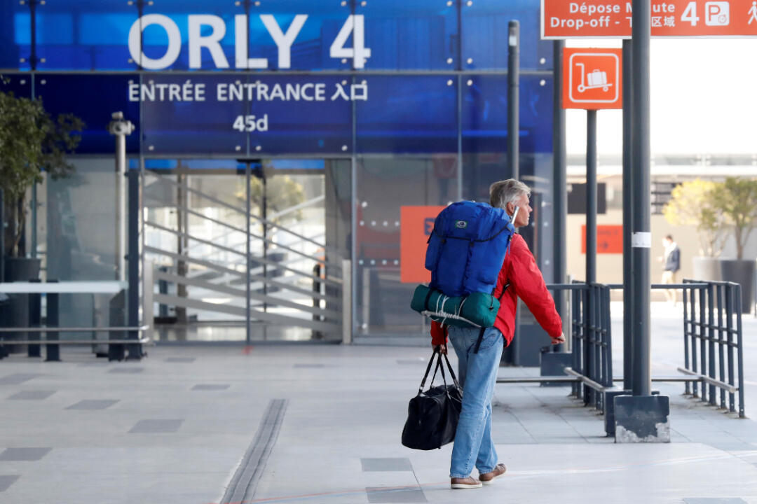 A passenger walks outside a terminal at Orly Airport near Paris at Orly Airport near Paris before its closing to commercial flights today, due to the spread of the coronavirus disease (COVID-19) in France, March 31, 2020.