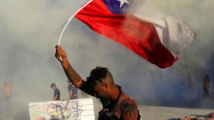 Un manifestant brandit le drapeau chilien lors d'un mouvement de protestation anti-gouvernement, le 9 novembre 2017 à Santiago.