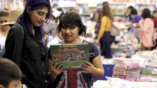 Dos mujeres hojean un libro en la última Feria Internacional del Libro de Guadalajara, el 5 de diciembre de 2019 en esa ciudad mexicana