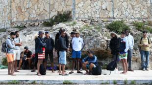 Un grupo de migrantes en Lampedusa, Italia, luego de desembarcar de un bote de madera en el que cruzaron el Mediterráneo desde África. 18 de octubre de 2019.