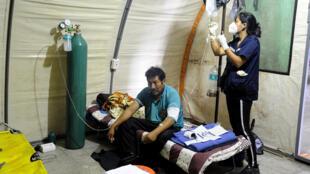 """Una voluntaria del grupo """"Ángeles contra el Covid"""" atiende a un paciente, el 13 de julio de 2020 en Santa Cruz (Bolivia)"""