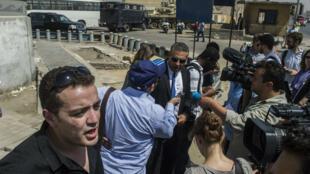 Les journalistes d'Al-Jazzera, Mohamed Fahmy (centre) and et Baher Mohamed (gauche), s'adressent aux médias devant la prison de Torah au Caire où devait se tenir leur procès le 30 juillet 2015. Le verdict a été reporté.