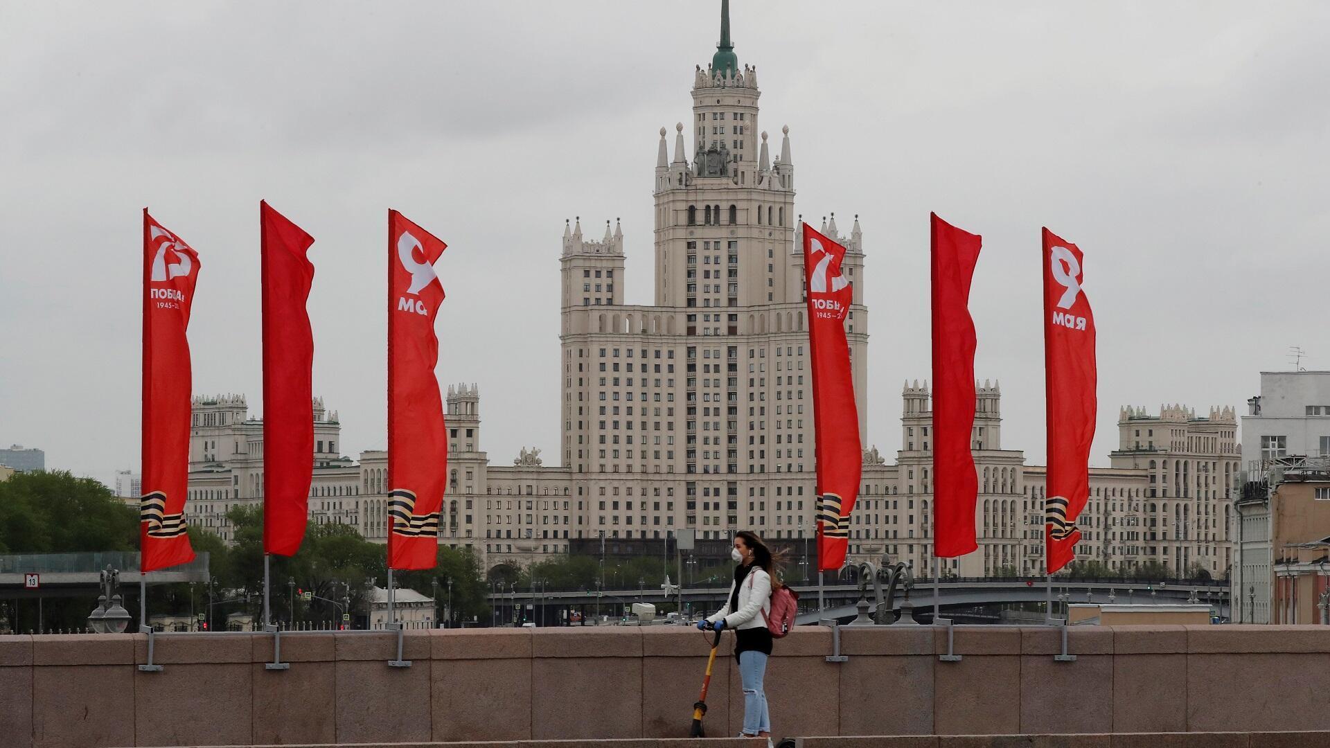 سيدة ترتدي قناعا طبيا تعبر جسرا بموسكو، 8 مايو/أيار 2020.