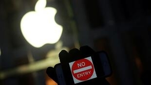 Photo d'archive montrant un manifestant brandissant son iPhone devant une boutique Apple en 2013