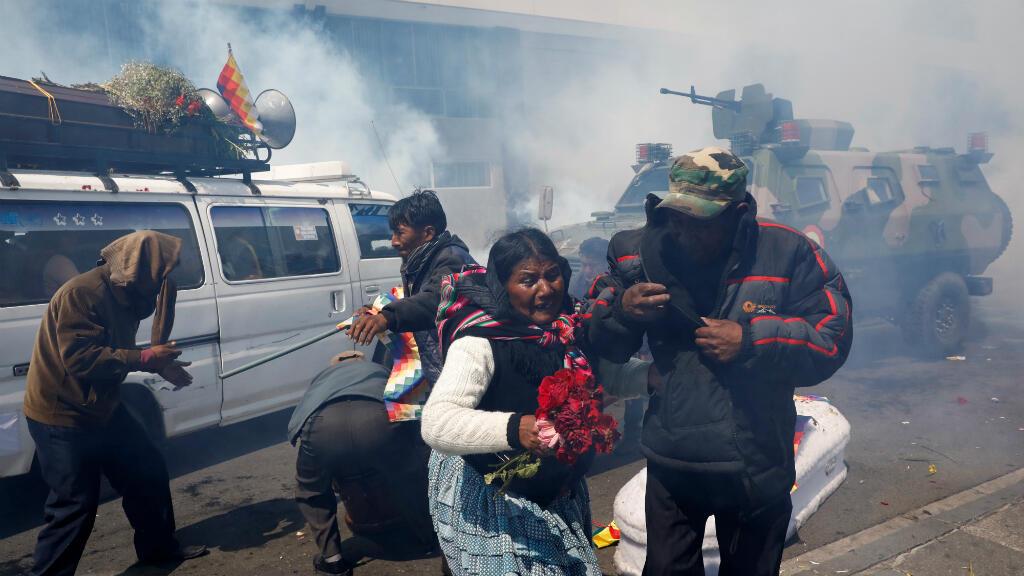 Los partidarios del expresidente de Bolivia Evo Morales se alejan de los ataúdes de las personas que fueron asesinadas durante los recientes enfrentamientos con las fuerzas de seguridad en Senkata, mientras la policía antidisturbios usa gases lacrimógenos durante una protesta en La Paz, Bolivia, el 21 de noviembre de 2019.