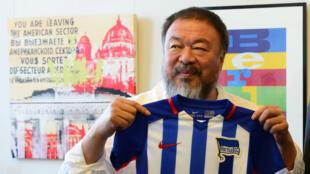 Ai Weiwei brandissant un maillot de l'équipe de football du Herta BSC Berlin offert par le maire de la ville, le 13 août 2015.