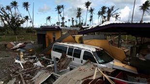 Un automóvil parcialmente enterrado debajo de los restos de una casa después de que el huracán María azotara la isla en septiembre de 2017, en Humacao, Puerto Rico.