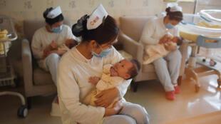 """Esta foto, tomada el 13 de diciembre de 2016, muestra a un grupo de enfermeras con bebés en el Centro Xiyuege, o """"Lucky Month Home"""", en Beijing."""