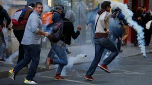 Des manifestants Gilets jaunes fuient les tirs de gaz lacrymogène de la police à Paris, le 21 septembre 2019.