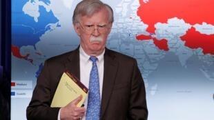 """El asesor de Seguridad Nacional de Estados Unidos, John Bolton, se dirige a reporteros durante una rueda de prensa en la Casa Blanca, el 28 de febrero de 2019, y deja ver en su libreta la anotación """"5.000 troops to Colombia""""."""