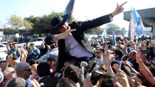 Jair Bolsonaro porté en triomphe par ses supporters à son arrivée à l'aéroport de Porto Alegre le 29 août 2018.