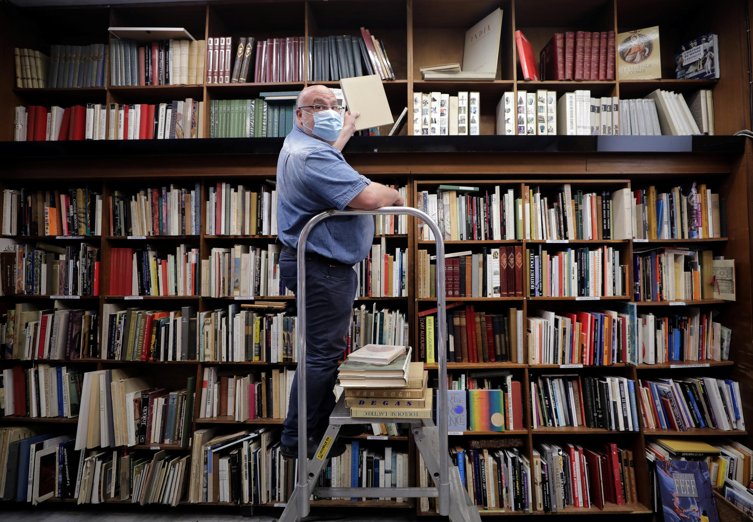 Bookseller Philippe Seyrat, wearing a protective face mask, arranges books at La Sorbonne bookshop in Nice on May 13, 2020.