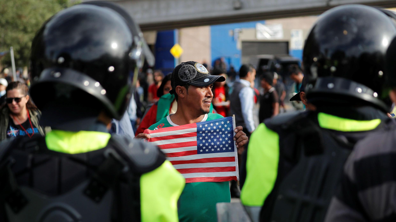 Un migrante, parte de una caravana de miles de personas que viajan desde América Central hacia Estados Unidos, porta una bandera estadounidense, mientras un grupo de migrantes negocia con la policía mexicana, cerca del puerto de entrada El Chaparral, en el cruce fronterizo entre México y Estados Unidos, Tijuana, México, el 22 de noviembre de 2018.