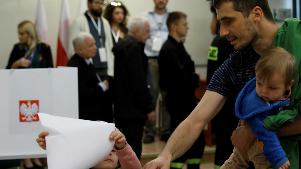 Un hombre asiste a una votación con sus hijos durante las elecciones parlamentarias en un colegio electoral en Varsovia, Polonia, el 13 de octubre de 2019.