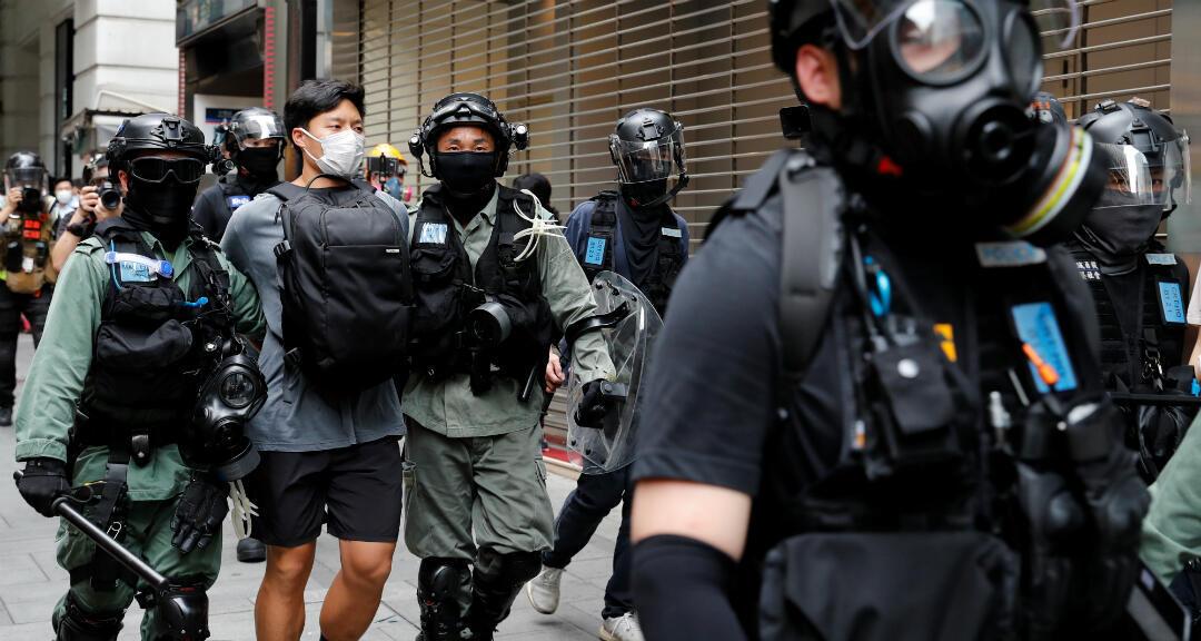 Agentes de la Policía antidisturbios detienen a un manifestante el 27 de mayo de 2020 durante una protesta en Honk Kong mientras se debate en el Parlamento la aprobación de una ley que busca penalizar las burlas al himno nacional chino.