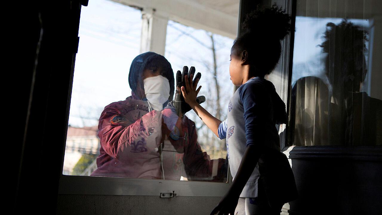 Un profesional sanitario saluda a su hija a través del vidrio para no exponerla al Covid-19 en Nueva York, Estados Unidos, el 11 de abril de 2020.