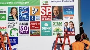 عمال يقومون بلصق أفيشات الدعاية الانتخابية للمترشحين في الانتخابات الأوروبية