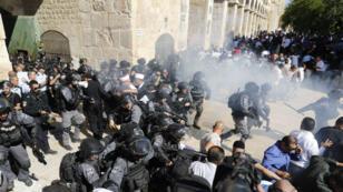 Des policiers israéliens tirent des grenades assourdissantes dans l'enceinte de la mosquée Al-Aqsa, à Jérusalem, le 11 août 2019.