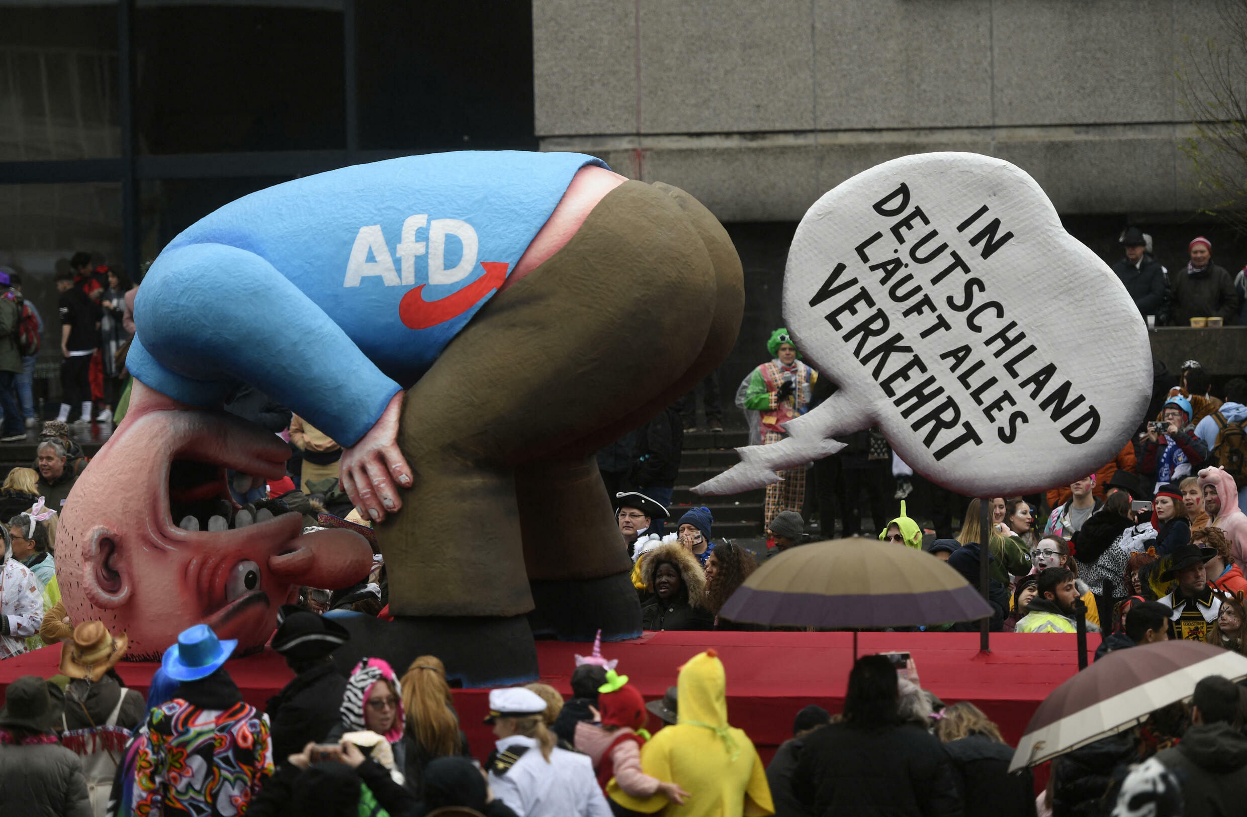 """""""Everything goes upside down in Germany,"""" says a supporter of the far-right AfD party at a carnival parade in Duesseldorf in February 2020."""