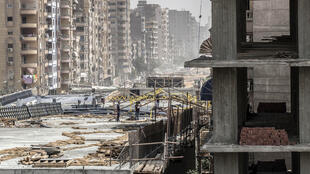 Construction of a road bridge in Cairo's Giza district almost touching lines of apartment buildings to the dismay of residents