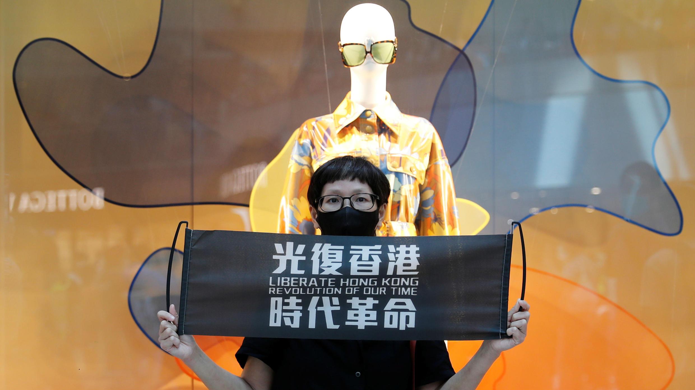 Una manifestante a favor de la democracia sostiene una pancarta que reza 'Liberad Hong Kong, la revolución de nuestro tiempo', durante una protesta para conmemorar el primer aniversario de una manifestación masiva contra el proyecto de Ley de Extradición, en Hong Kong, China, el 9 de junio de 2020.