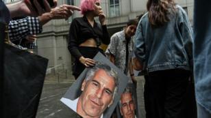 """Un groupe de militantes baptisé """"Hot Mess"""" brandissent des portraits de Jeffrey Epstein devant le tribunal fédéral de New York, le 8 juillet 2019."""