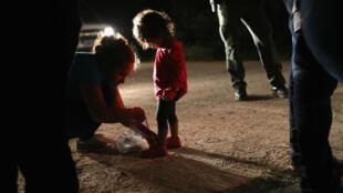 Une fillette hondurienne âgée de 2ans se voit retirer ses lacets de chaussures à la frontière mexicaine, le 12 juin 2018, à McAllen, Texas.