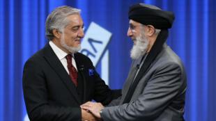 """Los candidatos presidenciales afganos Abdullah Abdullah y el ex """"señor de la guerra"""" Gulbuddin Hekmatyar se dan la mano antes del debate sobre las elecciones presidenciales en Kabul, Afganistán, el 25 de septiembre de 2019."""