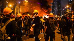 Des manifestants près d'une barricade incendiée le samedi 31 août.