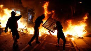 Manifestantes separatistas arrojan objetos al fuego durante una protesta en Barcelona, España, el 15 de octubre de 2019.