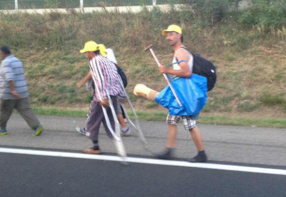 A man on crutches sets out on the long march from Budapest to Austria. (Photo: Fernande van Tets)