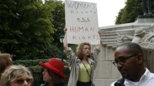 """Une manifestante porte une pancarte """"Les droits des femmes sont les droits humains"""", lors d'une manifestation à Paris, le 13 juillet 2017."""