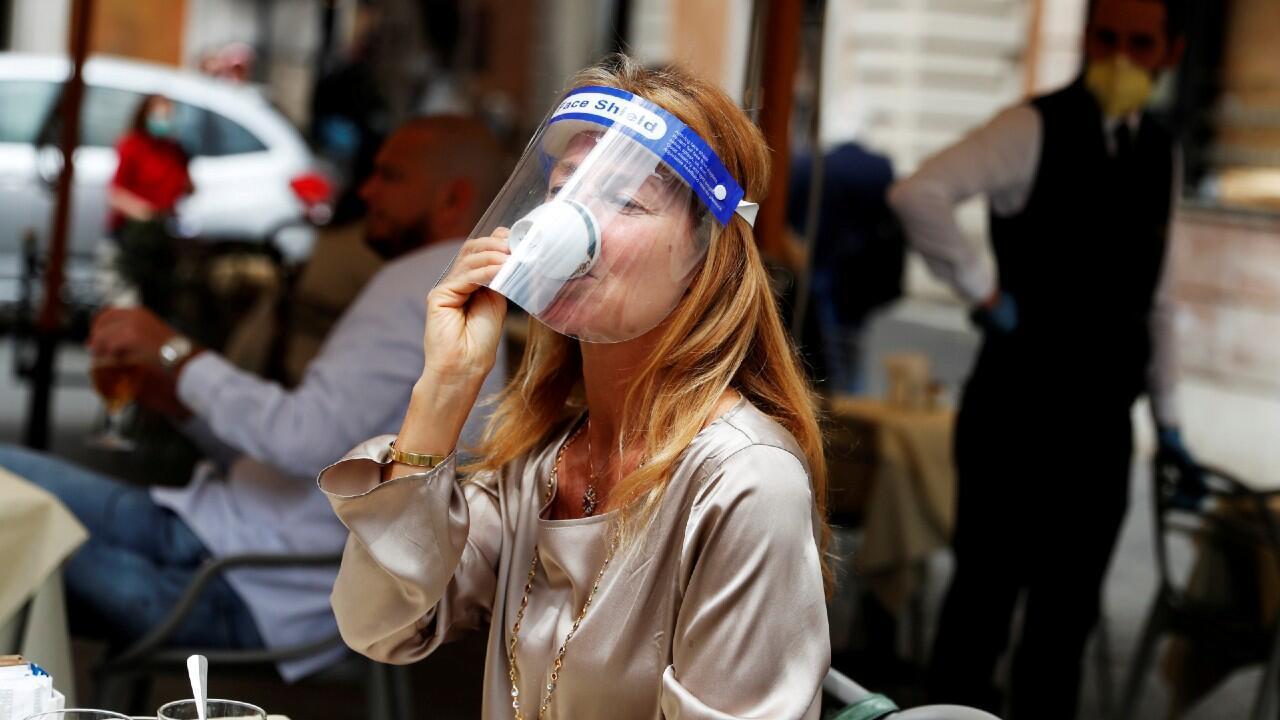 Una mujer que usa un protector facial degusta una taza de café en una cafetería romana durante el primer día de apertura de comercios y restaurantes en Italia desde el inicio de la epidemia. En Roma, Italia, el 18 de mayo de 2020.