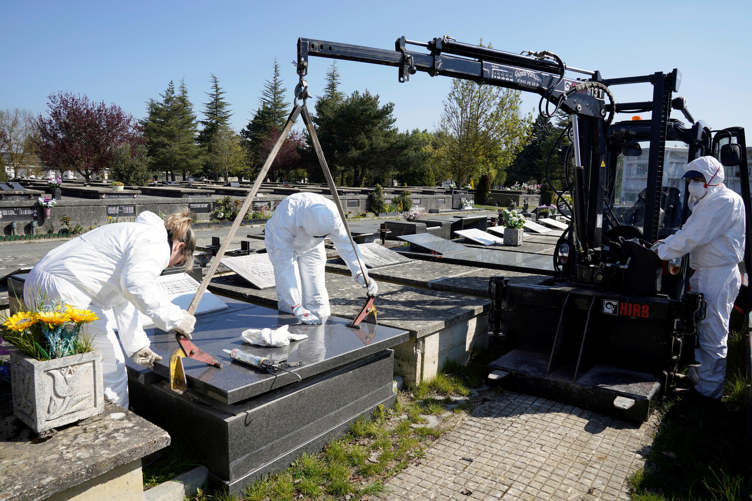 Municipal workers wearing protective gear seal the niche of a coronavirus disease (COVID-19) victim at El Salvador cemetery in Vitoria, Spain, March 27, 2020.