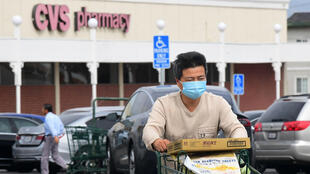 A man wears a facemask while pushing his shopping cart in Alhambra, California on February 27, 2020.