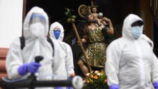 Trabajadores con equipo de protección personal se preparan para desinfectar un vehículo fuera de una iglesia durante la celebración del Día de San Cristóbal, en Ciudad de Guatemala, el 30 de julio de 2020