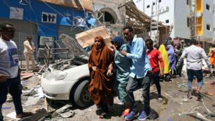 Un hombre evacúa a una mujer tras la explosión de un coche bomba en un centro comercial de Mogadiscio, el 4 de febrero de 2019.