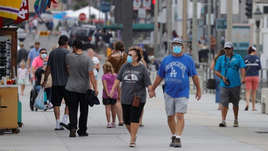 Archivo-Decenas de personas que usan mascarillas caminan a lo largo del muelle oceánico, mientras Estados Unidos pasó el jueves la barrera de los 4 millones de contagios, por Covid-19. En Huntington Beach, California, Estados Unidos, el 23 de julio de 2020.