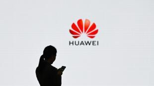 Una empleada de Huawei usa su teléfono móvil frente a un logotipo de la empresa durante un foro de transformación digital, el 6 de marzo de 2019 en la ciudad china de Shenzhen, vecina de Hong Kong