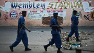 Des policiers burundais passent devant un pub de Bujumbura, le 25 mai 2015.