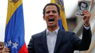 """El presidente de la Asamblea Nacional, Juan Guaidó, sostiene una imagen del libertador latinoamericano Simón Bolívar durante una jornada de protestas opositoras al Gobierno de Maduro en la que se autoproclamó """"presidente encargado de Venezuela"""". Caracas, Venezuela, el 23 de enero de 2018."""