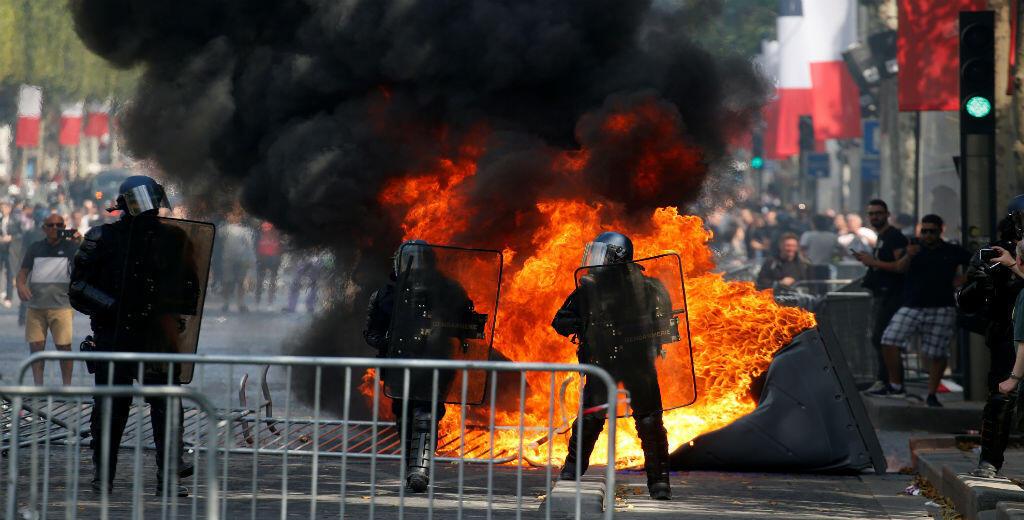 Gendarmes franceses durante los enfrentamientos con manifestantes en la Avenida de los Campos Elíseos después del tradicional desfile militar del Día de la Bastilla en París, Francia, el 14 de julio de 2019.